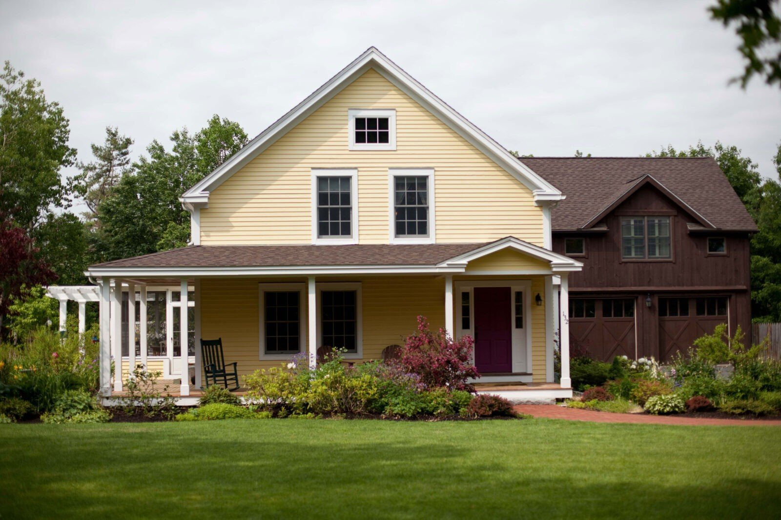 An idyllic post and beam farmhouse from yankee barn homes for Barn house plans with porches